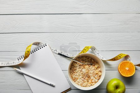 Photo for Top view of notebook with pencil, breakfast cereal in bowl, apple and orange near measuring tape on wooden white background with copy space - Royalty Free Image