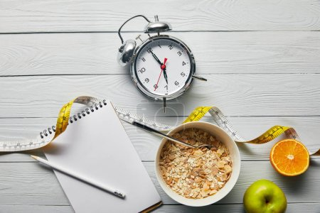 top view of alarm clock, notebook with pencil, breakfast cereal in bowl, apple and orange near measuring tape on wooden white background