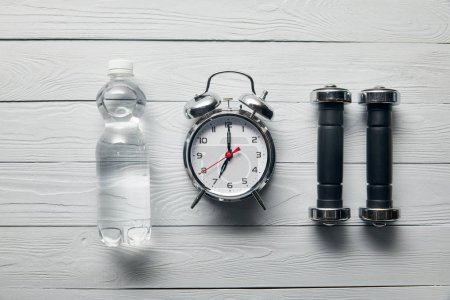 flat lay with silver alarm clock, bottle of water and dumbbells on wooden white background
