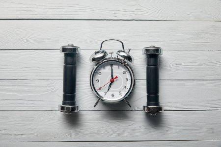 pose plate avec réveil argenté et haltères noires sur fond blanc en bois