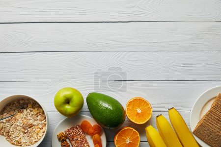 Photo for Top view of breakfast cereal in bowl, nuts, crispbread and ripe fruits on wooden white background with copy space - Royalty Free Image