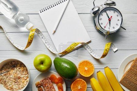vista superior de alimentos dietéticos cerca del reloj despertador, cinta métrica, cuaderno y agua sobre fondo blanco de madera