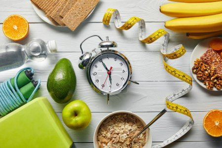 Photo for Top view of diet food near measuring tape, alarm clock and sport equipment on wooden white background - Royalty Free Image
