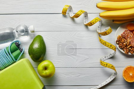Photo for Top view of diet food near measuring tape and sport equipment on wooden white table with copy space - Royalty Free Image