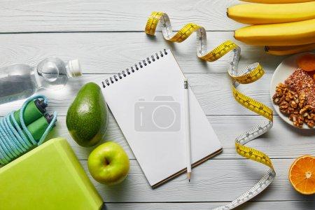 Photo pour Vue supérieure de la nourriture de régime près de la bande de mesure, de cahier et d'équipement de sport sur le fond blanc en bois - image libre de droit