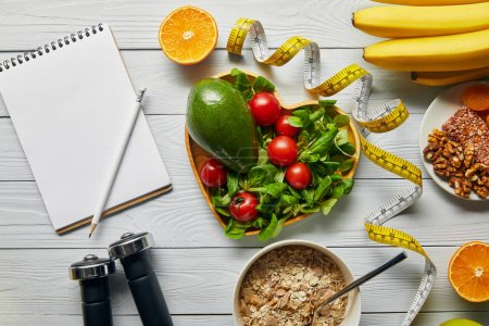 top view of measuring tape, cereal, fruits and vegetables in heart-shaped bowl and dumbbells near blank notebook on wooden white background