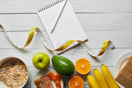 Photo for Top view of measuring tape, diet food and blank notebook on wooden white background - Royalty Free Image