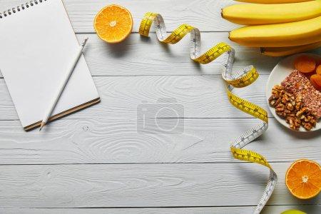 Photo pour Vue du dessus du ruban à mesurer, des aliments diététiques et du carnet vierge sur fond blanc en bois avec espace de copie - image libre de droit