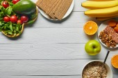 "Постер, картина, фотообои ""top view of fresh fruits, vegetables and cereal on wooden white background with copy space"""