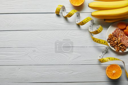 Photo for Top view of fresh fruits, measuring tape and nuts on wooden white background with copy space - Royalty Free Image
