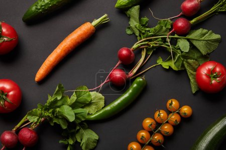 Photo for Raw nutritious tasty vegetables with green leaves on black background - Royalty Free Image