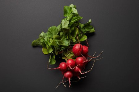 Photo for Top view of raw nutritious tasty radish with green leaves on black background - Royalty Free Image