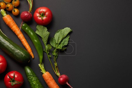 Photo for Top view of raw tasty vegetables with green leaves on black background with copy space - Royalty Free Image