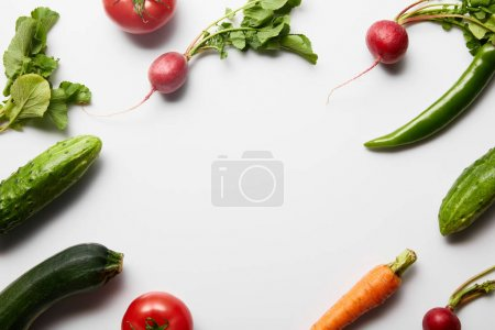 Photo for Top view of raw tasty vegetables with green leaves on white background with copy space - Royalty Free Image