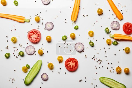Photo for Top view of organic sliced vegetables and black pepper on white background - Royalty Free Image