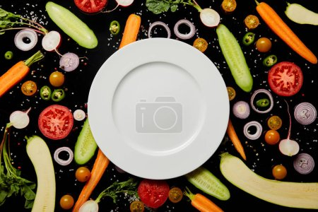Photo for Top view of empty round plate on vegetable pattern background with salt isolated on black - Royalty Free Image