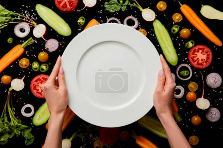 Photo for Cropped view of woman holding empty round plate on vegetable pattern background isolated on black - Royalty Free Image