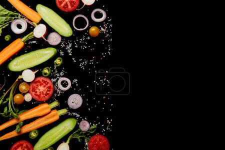 top view of fresh vegetable slices with scattered salt isolated on black with copy space
