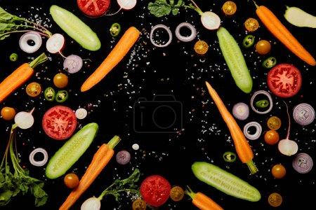 vue de dessus des tranches de légumes frais dispersés avec du sel isolé sur noir