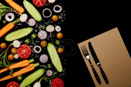 top view of fresh vegetable slices with salt near paper blank and cutlery isolated on black with copy space