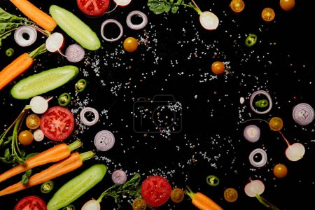 top view of fresh cut vegetables with salt isolated on black with copy space
