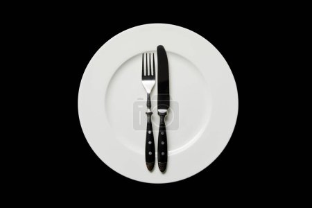 Photo for Top view of white round plate with knife and fork isolated on black - Royalty Free Image