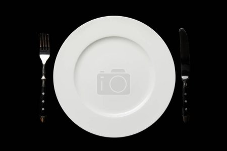 Photo for Top view of white empty round plate and knife with fork isolated on black - Royalty Free Image