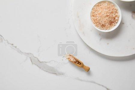 Foto de Vista superior de la sal marina en un tazón sobre una mesa de mármol cerca de una espátula de madera - Imagen libre de derechos