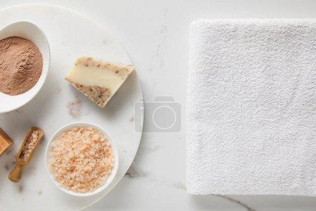 Photo pour Vue supérieure de poudre d'argile, sel de mer et savon sur la table de marbre près de la serviette blanche de coton - image libre de droit