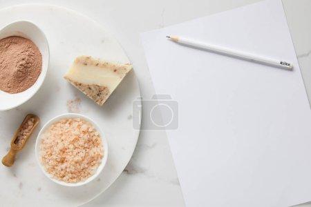 Foto de Vista superior de polvo de arcilla, jabón y sal marina en la mesa de mármol cerca de papel blanco y lápiz - Imagen libre de derechos