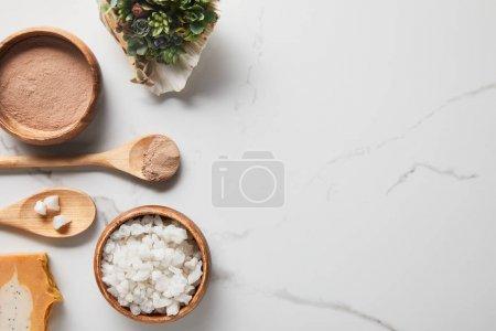 Photo pour Vue supérieure de poudre d'argile et sel de mer dans des cuvettes et des cuillères en bois sur la table de marbre près du savon succulent et - image libre de droit