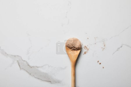 Photo for Top view of clay powder in wooden spoon on marble table - Royalty Free Image