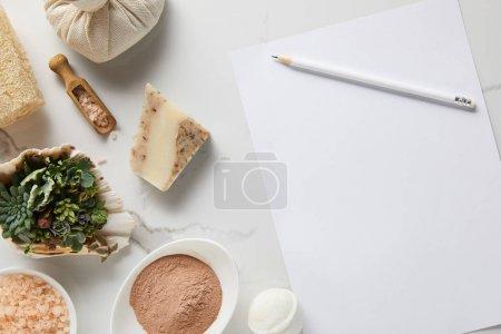 Photo pour Vue supérieure des cosmétiques organiques et du papier blanc avec le crayon sur la table de marbre - image libre de droit