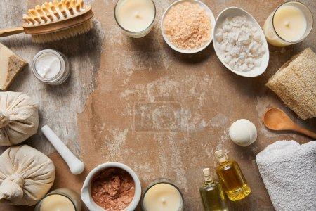 Draufsicht auf natürliche kosmetische Inhaltsstoffe und Schönheitsmittel in der Nähe von Dekorkerzen auf texturierter verwitterter beiger Oberfläche