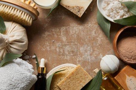 Photo pour Vue du haut des cosmétiques organiques et des approvisionnements de beauté sur la surface beige altérée texturée avec les feuilles vertes - image libre de droit