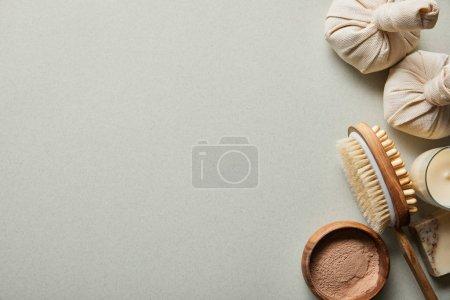 Photo pour Vue supérieure de poudre d'argile dans le bol en bois près de la brosse de massage, bougie sur le fond blanc - image libre de droit