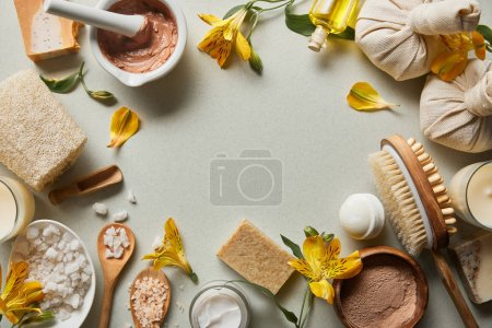 top view of organic cosmetics and beauty supplies on white background with candles and yellow flowers