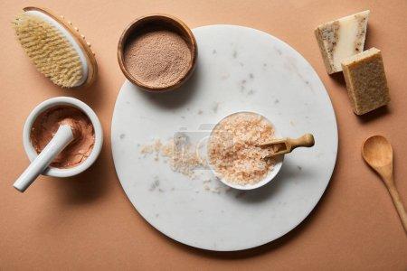 Photo pour Vue supérieure de l'argile, brosse de massage en bois, cuillère et savon sur le fond beige près du sel de mer dans le bol sur le cercle de marbre - image libre de droit