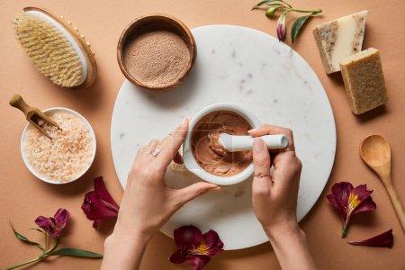 Photo pour Vue recadrée de femme mélangeant l'argile dans l'abol sur le cercle de marbre près des ingrédients cosmétiques organiques sur le fond beige avec les pétales dispersés de fleur - image libre de droit