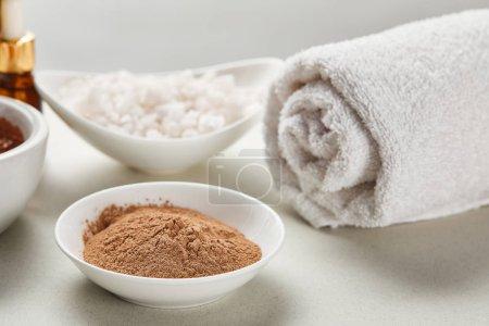 Foto de Enfoque selectivo de polvo de arcilla y sal marina en cuencos cerca de la toalla de algodón laminado blanco aislado en gris - Imagen libre de derechos