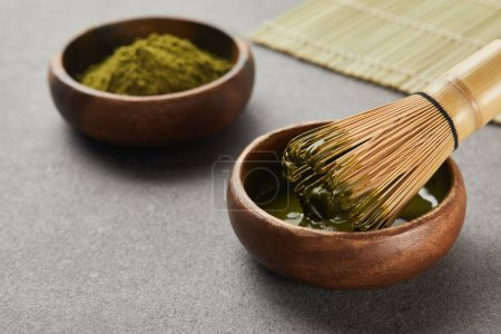 Photo for Selective focus of matcha powder bowl near bamboo whisk in green tea - Royalty Free Image