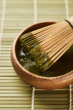 Photo for Selective focus of green matcha powder and bamboo whisk in wooden bowl on table mat - Royalty Free Image