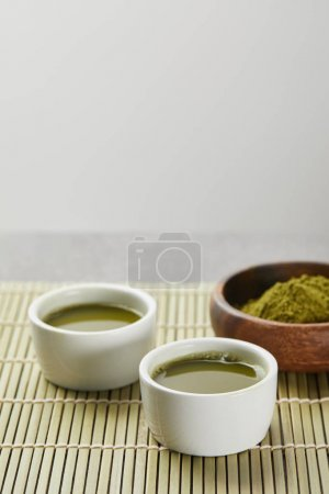 Photo for Selective focus of green matcha powder in wooden bowl near white cups with tea on bamboo table mat - Royalty Free Image