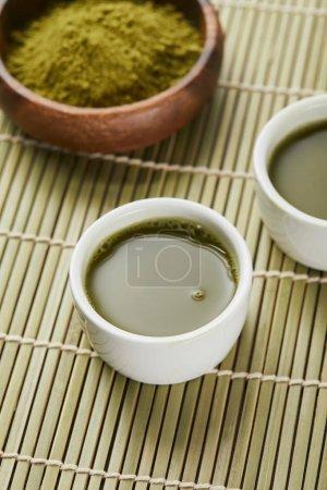 Photo pour Foyer sélectif de poudre verte de matcha dans le bol en bois près des tasses blanches avec le thé sur le tapis de table en bambou - image libre de droit