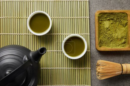 top view of white cups with green tea near black teapot on bamboo table mat with matcha powder on wooden board