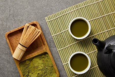 Photo for Top view of green matcha powder with bamboo whisk in wooden board near teapot and white cups with green tea on table mat - Royalty Free Image