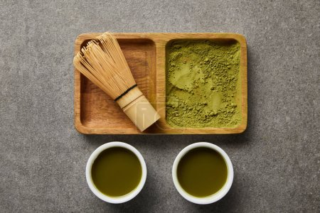 Photo for Top view of bamboo whisk and matcha powder on wooden bowl near white cups with green tea - Royalty Free Image