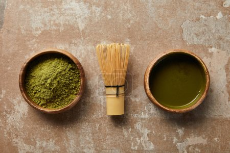 Photo for Top view of matcha tea and powder in wooden bowl with bamboo whisk on aged surface - Royalty Free Image