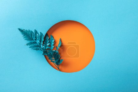 Photo for Blue decorative leaf in orange round hole on blue paper - Royalty Free Image