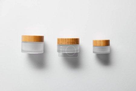Photo pour Trois pots vides pour crème pour les mains sur blanc - image libre de droit